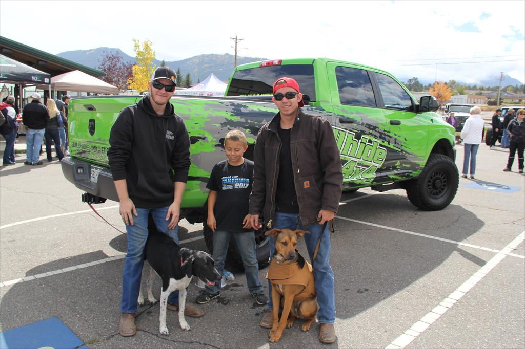 People and their dogs in front of a Green Pick Up Truck