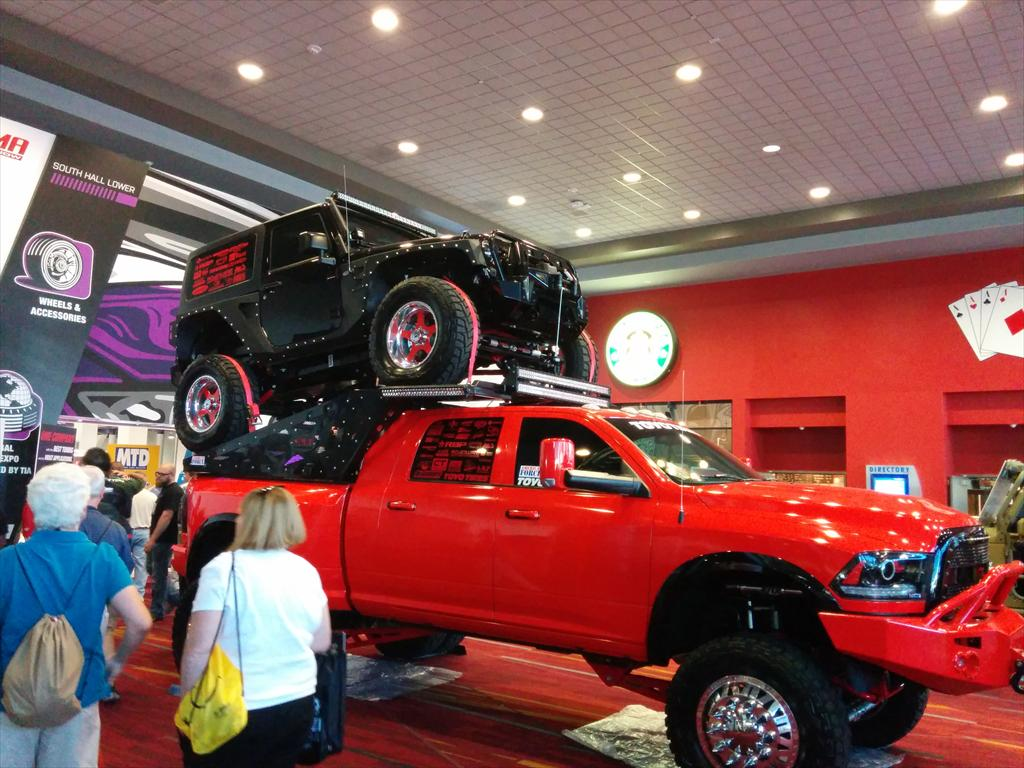 Red truck with black car on top of it